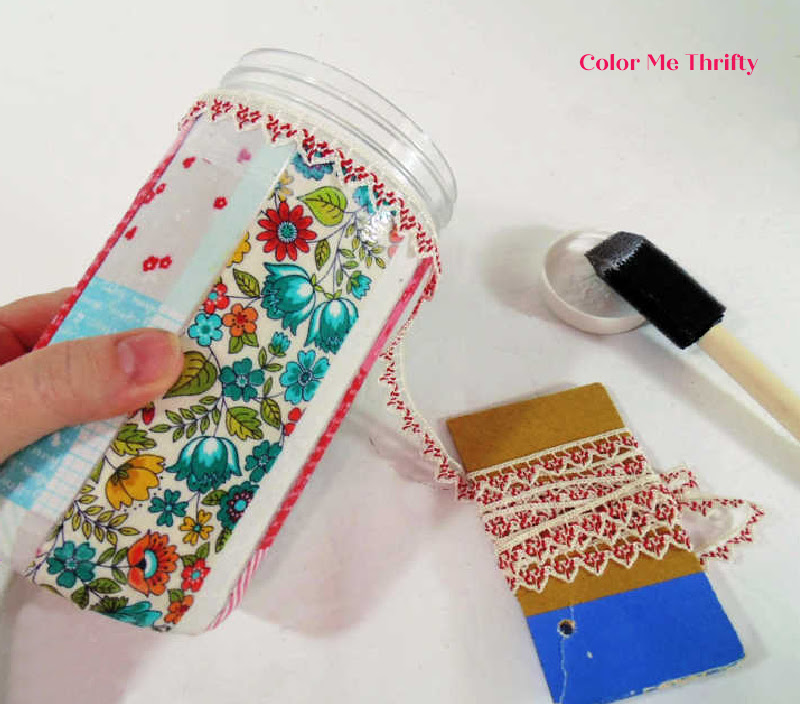 gluing ribbon at top edge of decoupaged peanut butter jars
