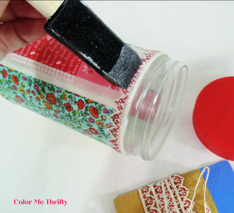 using decoupage medium to affix ribbon in place at top of peanut butter jars